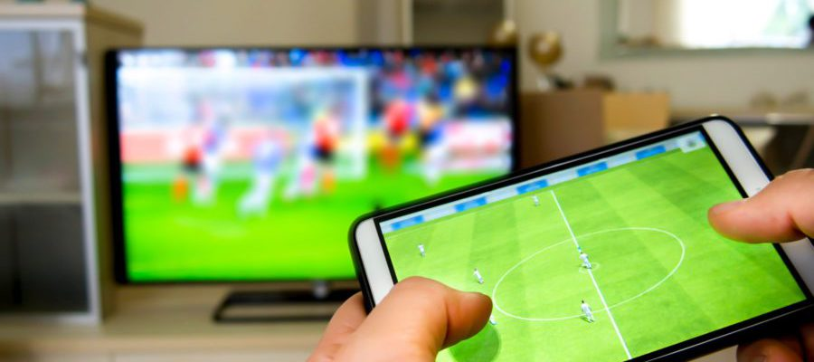 Synced Multiscreen Experience - Person holding a smartphone infront of a TV