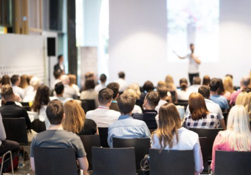 Applications > Conferences - image of an audience watching a presentation