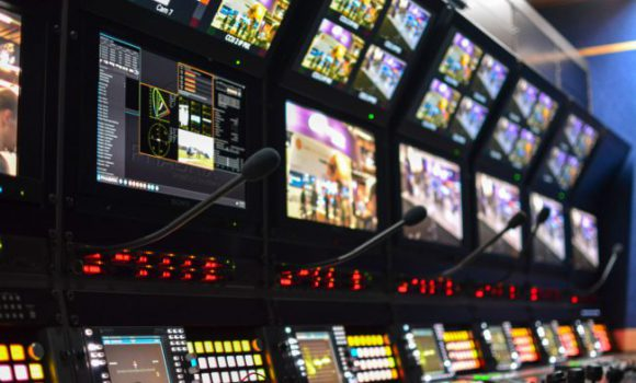Solutions > Synced Remote Production - a bank of screens in a production gallery
