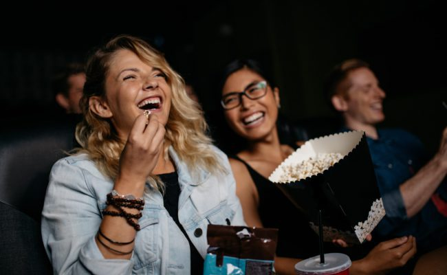 Applications > Cinema - image of people enjoying popcorn in a cinema